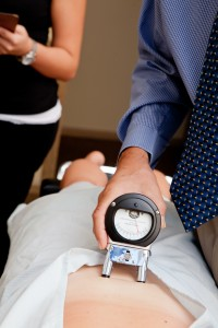 Dr. Brusbeen using a device to examine a patient's lower back