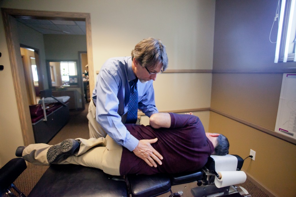 Dr. Brusveen adjusting a patient laying on an adjustment table