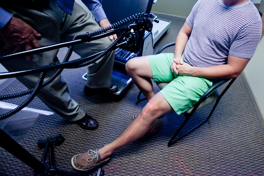 Dr. Brusveen using a cold laser therapy machine on a patients knee